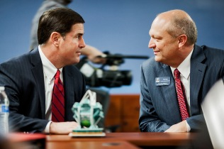 Gov. Doug Ducey visits with former Arizona Senate President Tim Bee at the University of Arizona in Tucson, Ariz.