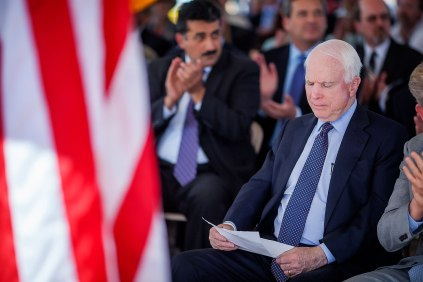 Senator John McCain reads over his speech before being introduced at the groundbreaking for the new parkway in Tucson, Ariz.
