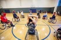 Fabrizio Shao, a UA freshman and pointguard for the men's wheelchair basketball team, leads the veterans for the GPS sports camp in warm up stretches. Photograph by John de Dios/UANews